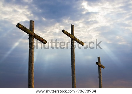 Three wooden crosses stand against a dramatic evening sky with radiant beams penetrating clouds. Great for Easter Sunday! - stock photo