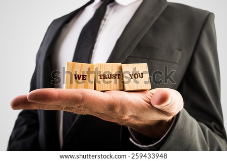 Three wooden cubes aligned on a male hand with the words We trust you.
