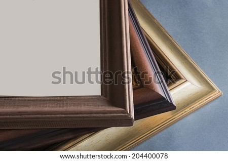 Three wooden frames on blue-gray background