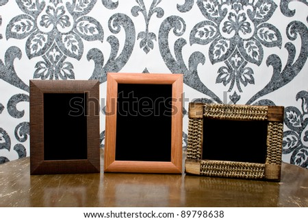 Three wooden photo frames on old table on vintage wallpaper background - stock photo