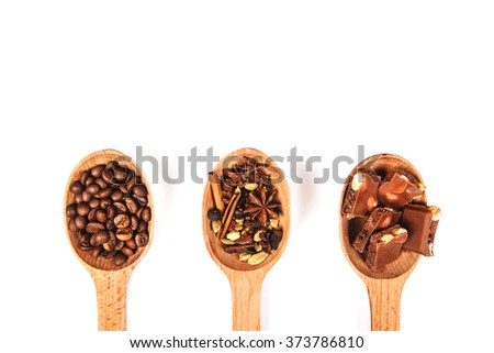 Three wooden spoons with coffee beans, chocolate and spices for mulled wine or dessert, or hot chocolate, isolated on white - stock photo