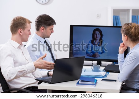 Three workers having business conference online with colleague - stock photo