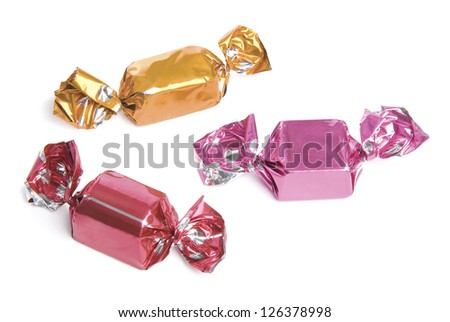Three wrapped candies or sweets on a white background. - stock photo