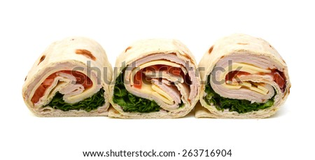 three wrapped tortilla sandwich rolls cut on white background