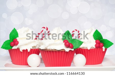 Three Xmas cupcakes with whipped cream and decoration on bokeh background