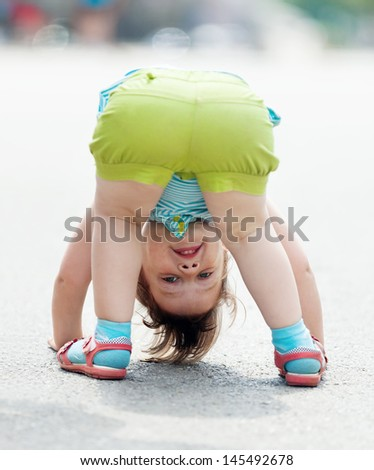 three-year baby girl playing upside down in street - stock photo
