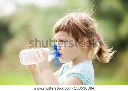 three year child drinking from plastic bottle - stock photo