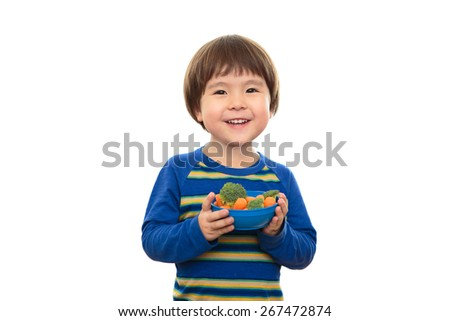 Three year old boy isolated on white background holding bowl of vegetables, carrots and broccoli. Smiling, happy, bright preschooler eating healthy snacks with a natural expression. Happy and healthy. - stock photo