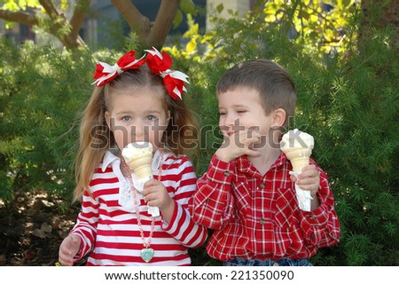 three year old girl and four year old boy eating ice cream having fun on a cold December day in California - stock photo