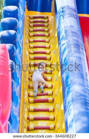 Three year old girl climbs the stairs to the high hill inflatable trampoline