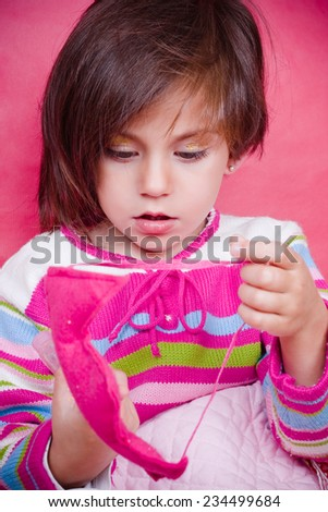 Three year old girl playing with a pink crown fabric - stock photo