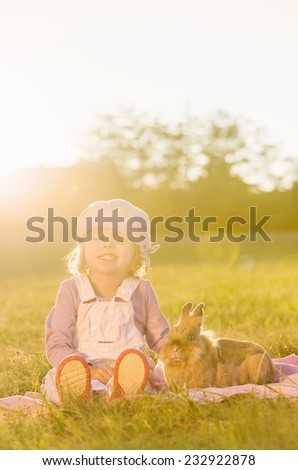 Three year old girl sitting with rabbit on meadow