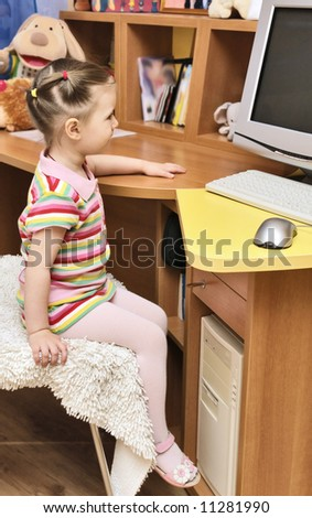 three year old girl watching cartoons on computer in her room