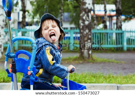 Three year old kid playing outdoor on tricycle.