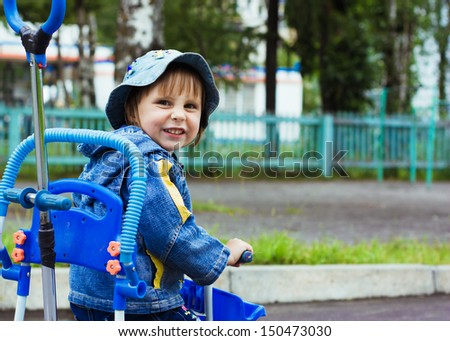 Three year old kid playing outdoor on tricycle. - stock photo