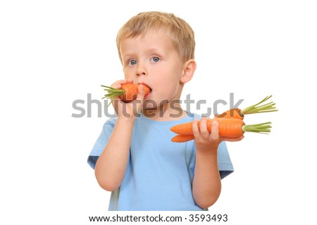 three years old boy eating fresh carrot isolated on white
