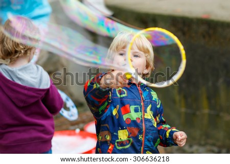 Three years old caucasian toddler boy blowing soap bubbles outdoor on birthday party - happy carefree childhood. Kid having fun. - stock photo