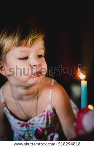 Three years old girl blowing candles