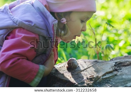 Three years old preschooler is looking and blowing on crawling edible snail - stock photo