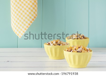Three yellow bowls with cereals on a white wooden table with a robin egg blue background with a yellow checkered napkin. Vintage style. - stock photo