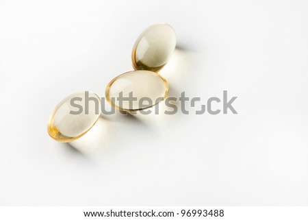 Three yellow pills on white background - stock photo