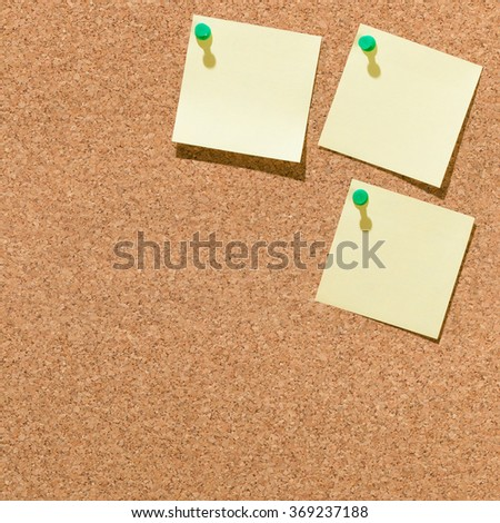 Three yellow square slips of paper pinned on brown cork board with space for text; Memory aid - stock photo