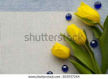 Three yellow tulips are in the lower right corner on the blue textile fabric. Blue glass stones are loose. - stock photo