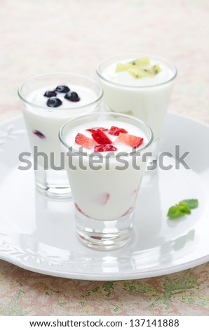 three yogurt with fruit in a glass beaker on a plate vertical - stock photo