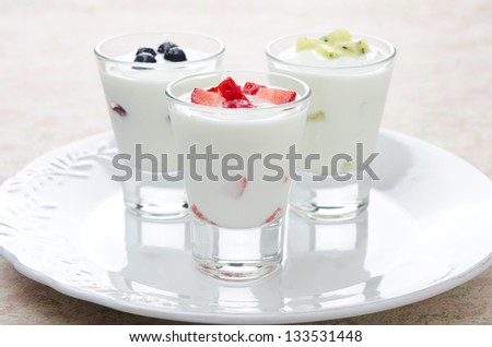 three yogurt with various fruits on a plate - stock photo