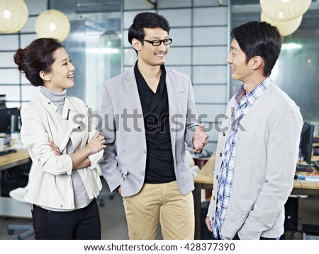 three young asian business people standing in office chatting. - stock photo
