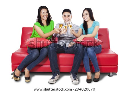 Three young asian people drinking champagne together on the couch, isolated on white background - stock photo