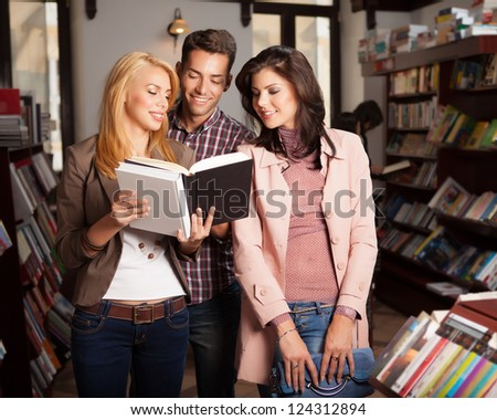 three young attractive people in a bookshop, one of them holding an opened book in her hands and reading from it, with many bookshelves in background - stock photo