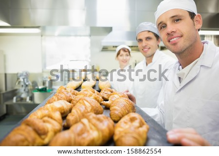 Three young bakers posing in a bakery smiling at the camera - stock photo