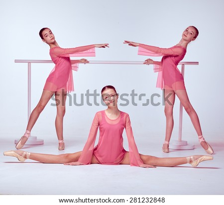 Three young ballerinas  in a pink dresses stretching on the bar on beige background - stock photo