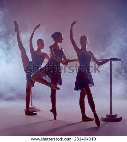 Three young ballerinas  in blue dresses stretching on the bar on lilac background - stock photo