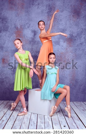 Three young ballerinas in colorful dresses posing on lilac wooden floor background - stock photo
