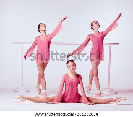 Three young ballerinas stretching on the bar on beige background - stock photo