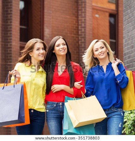 Three young beautiful female friends walking with shopping bags in city center.