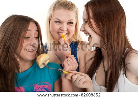 three young beautiful girl eating fruit, isolated over white - stock photo