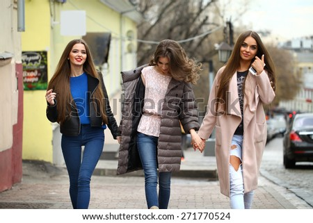 Three young beautiful girlfriends in autumn clothes walking down the street - stock photo