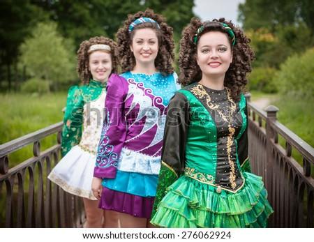 Three young beautiful girls in irish dance dress and wig posing outdoor - stock photo