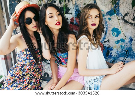 three young beautiful girls rest at a bus stop - stock photo