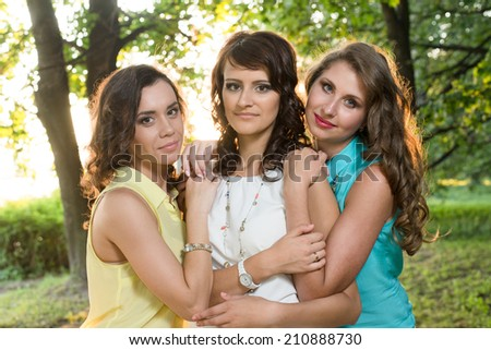 Three young beautiful ladies posing during walk in the city park near bank of the river on a sunset light.