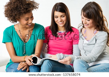 Three Young Beautiful Smiling Women Reading Magazine News