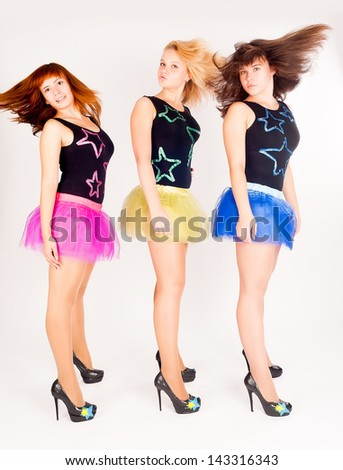 Three young beautiful women from dancing group at white background