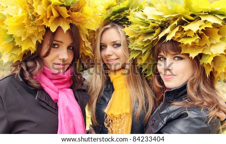 Three young beautiful women in the wreaths from leaves