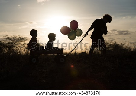Three young boys in silhouette playing on hill - stock photo