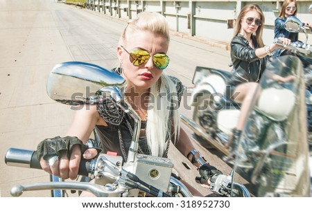 Three Young brutal cute girl lie on chopper and wear black leather dress and stylish sunglasses Empty space for inscription 3 Biker Woman on motorcycle against metal bridge background Blond female - stock photo