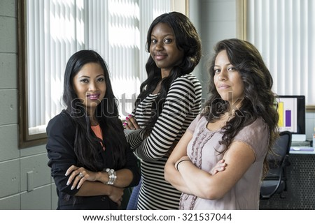 Three young business women standing in an office, arms crossed, smiling - stock photo