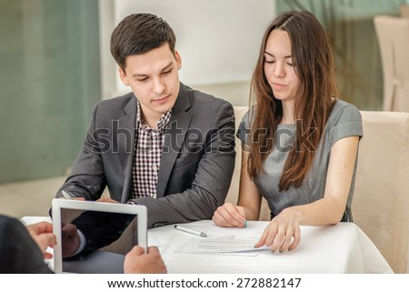 Three young businessman sitting at the table and discussing business affairs.Successful businessmen discussing business on a tablet.Couple man and woman sitting at the table and smiling to each other